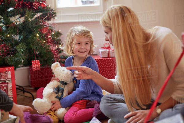 A mother and daughter unwrapping presents under a Christmas tree, holding a teddy bear.  Royalty-free stock photo