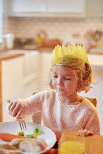 A young girl wearing a party hat, sitting at a table having a meal.  Royalty-free stock photo