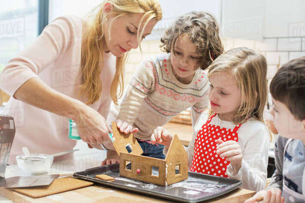 A woman and three children creating a baked gingerbread house.  Royalty-free stock photo