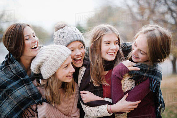 Five young people, girls, friends in warm shawls and woolly hats outdoors. Royalty-free stock photo