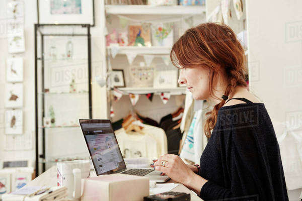 A woman in a small crafts supplier and gift shop, using a laptop, working,  Royalty-free stock photo