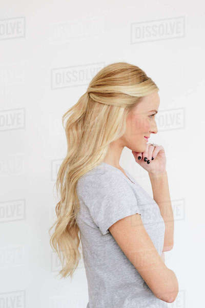 A young woman with long blond wavy hair. Side view.  Royalty-free stock photo