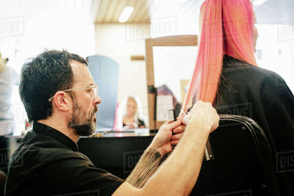 A hair stylist with a client, trimming the ends of her long dyed pink straight hair. Royalty-free stock photo
