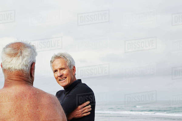 Two senior men standing on a beach chatting, one wearing a wetsuit.  Royalty-free stock photo