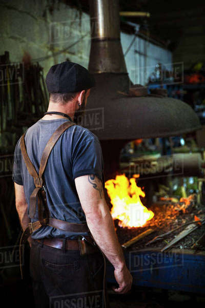 A blacksmith wearing a leather apron stands in front of a furnace in a workshop. Royalty-free stock photo