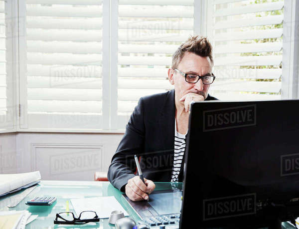 A man wearing glasses sitting at a desk in an office looking at a computer screen.   Royalty-free stock photo
