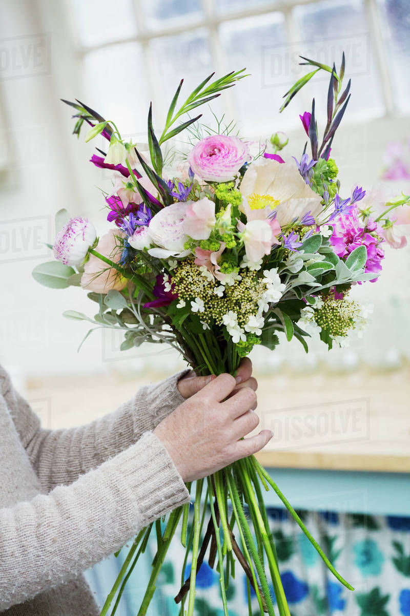 A florist creating a hand tied bunch of fresh flowers stock photo a florist creating a hand tied bunch of fresh flowers izmirmasajfo
