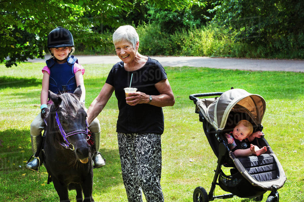 Woman Baby In Pushchair And Blond Girl Wearing Riding Hat D102478003