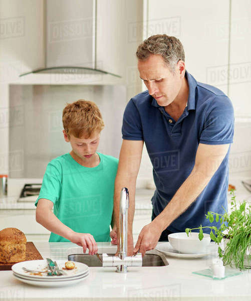 A family home. A man and a young boy in the kitchen side by side doing the dishes.  Royalty-free stock photo