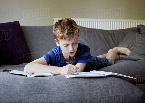 A family home. A boy lying on his front on a sofa doing his homework, writing in an exercise book. Royalty-free stock photo