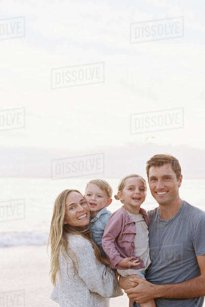 Couple standing with their son and daughter on a sandy beach by the ocean, looking at camera, smiling. Royalty-free stock photo