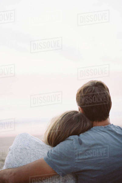 A couple sitting looking out to the ocean, back view, arms around each other.  Royalty-free stock photo