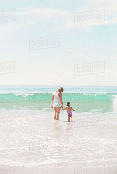 Woman standing hand in hand with her daughter on a sandy beach watching a wave. Royalty-free stock photo