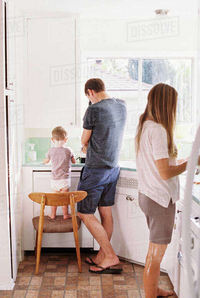 Couple standing in a kitchen, their son standing on a chair beside them. Royalty-free stock photo