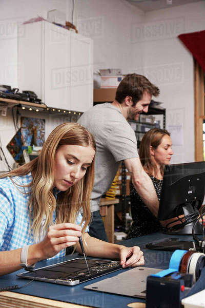 A man standing behind two women sitting working on circuitry in a technology lab. Royalty-free stock photo