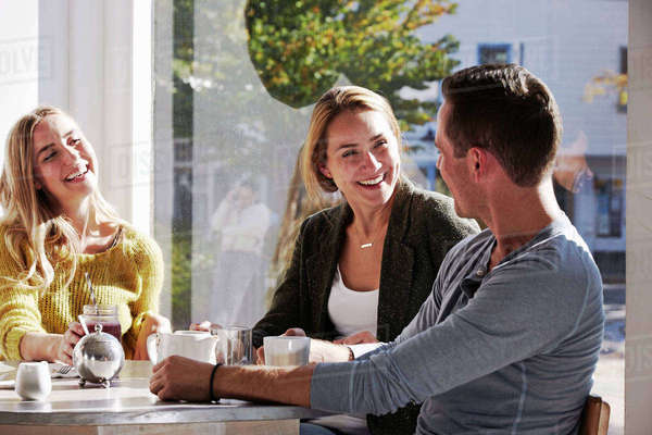 Three people sitting at a table talking, with mugs and jars of smoothies. Royalty-free stock photo