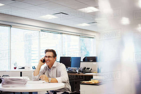 A man sitting at a table in an office, holding a phone to his head and smiling. Royalty-free stock photo