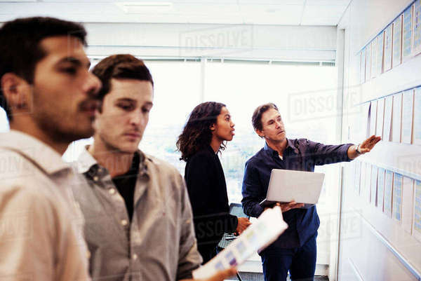 A woman and three men standing in an office looking at a display on a wall. Royalty-free stock photo