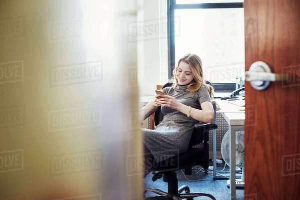 A woman in an office sitting checking her phone, seen through an open door.  Royalty-free stock photo