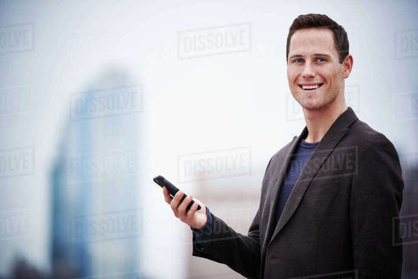 A young man standing on a rooftop holding a cellphone. Royalty-free stock photo