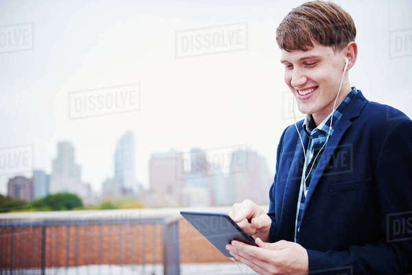 A young man standing on a rooftop looking down at a tablet. Royalty-free stock photo