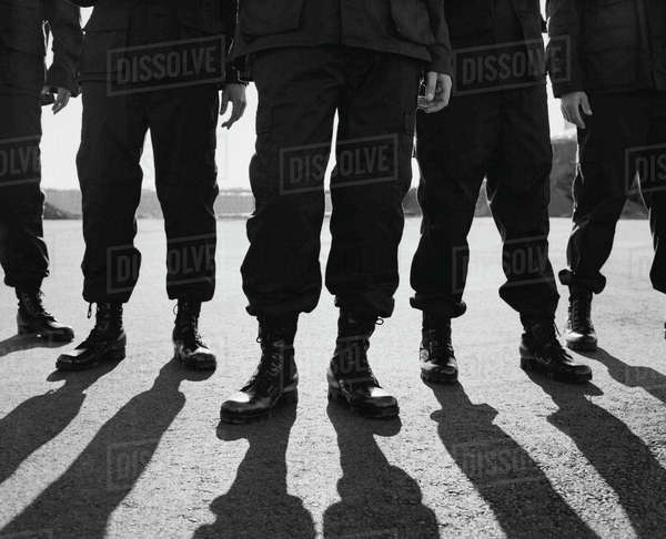Low angle view of row of men wearing military uniforms, casting shadows Royalty-free stock photo