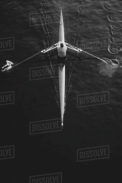 A man sculling in a single scull rowing boat, on the water.  Overhead view.  Royalty-free stock photo