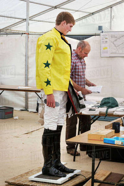 Jockey in a yellow shirt standing on weighing scale, being weighed before a horse race. Royalty-free stock photo