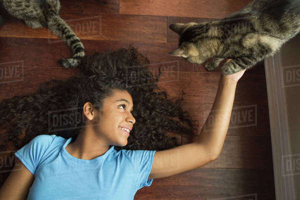 A girl lying on her back stroking a cat.  Royalty-free stock photo