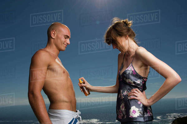Shirtless man and woman standing in front of ocean, woman applying suntan lotion to man's stomach. Royalty-free stock photo