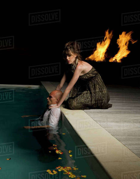 Woman kneeling on the edge of a swimming pool, touching shoulders of man inside pool, flames in the background. Royalty-free stock photo