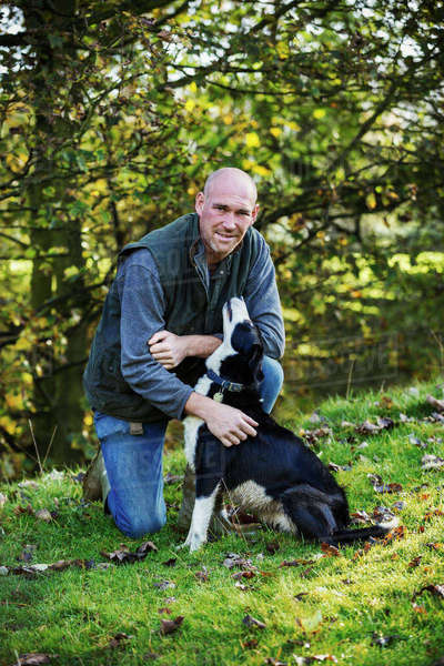 Sheep farmer kneeling on a meadow patting his black and white sheepdog. Royalty-free stock photo