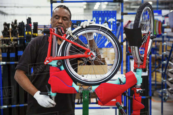 Male skilled factory worker assembling a bicycle in a factory, attaching a wheel. Royalty-free stock photo