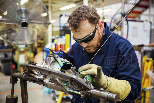 Male skilled factory worker wearing eye protectors welding a bicycle part in a factory. Royalty-free stock photo