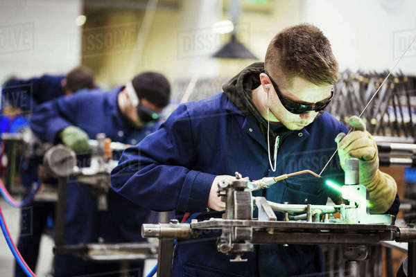 Male skilled factory worker wearing protective glasses, welding part of a bicycle together in a factory. Royalty-free stock photo