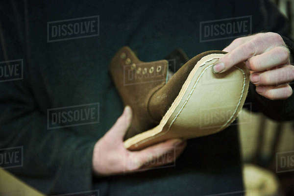 Close up of worker in a shoemaker's workshop, attaching a sole to a leather boot. Royalty-free stock photo