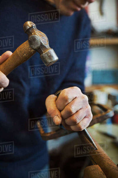 Man standing in a workshop, holding a hammer and wood chisel, working on a piece of wood. Royalty-free stock photo