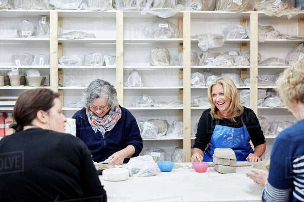 A group of four women chatting together and working on their pots in a pottery studio.  Royalty-free stock photo