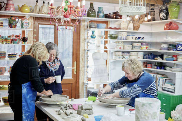 Three women in a pottery studio working with clay.  Royalty-free stock photo