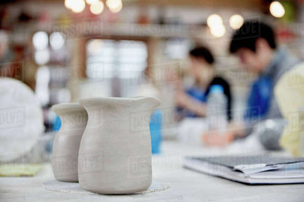 Two clay jugs in the foreground. A ceramics class taking place, people seated at a workbench in a pottery studio.  Royalty-free stock photo