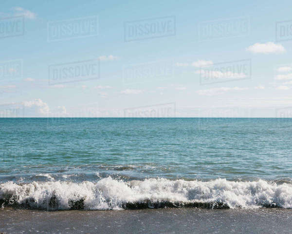 A sandy beach and waves breaking on the shore, and view to the horizon. Light wispy clouds.  Royalty-free stock photo
