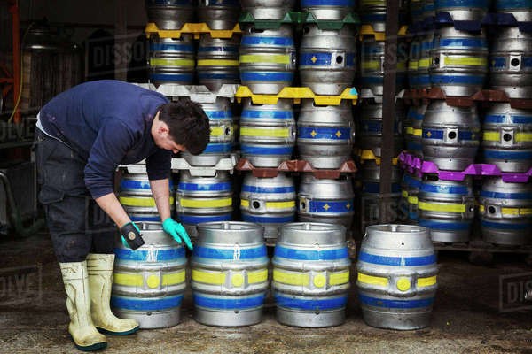 Man working in a brewery, standing next to a stack of metal beer kegs, holding mallet. Royalty-free stock photo