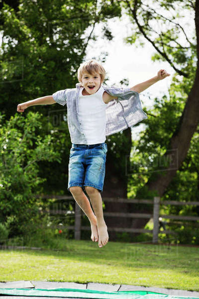 Boy wearing shirt and denim shorts jumping on a trampoline in a garden. Royalty-free stock photo