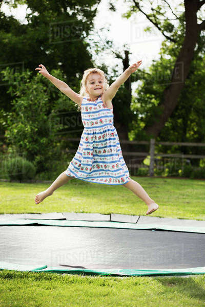 Girl in a sundress jumping on a trampoline set in the ground, in a garden. Royalty-free stock photo