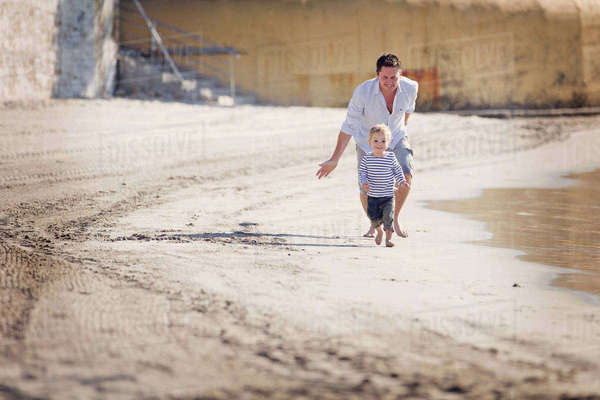 Man wearing shorts chasing smiling young boy along a sandy beach. Royalty-free stock photo