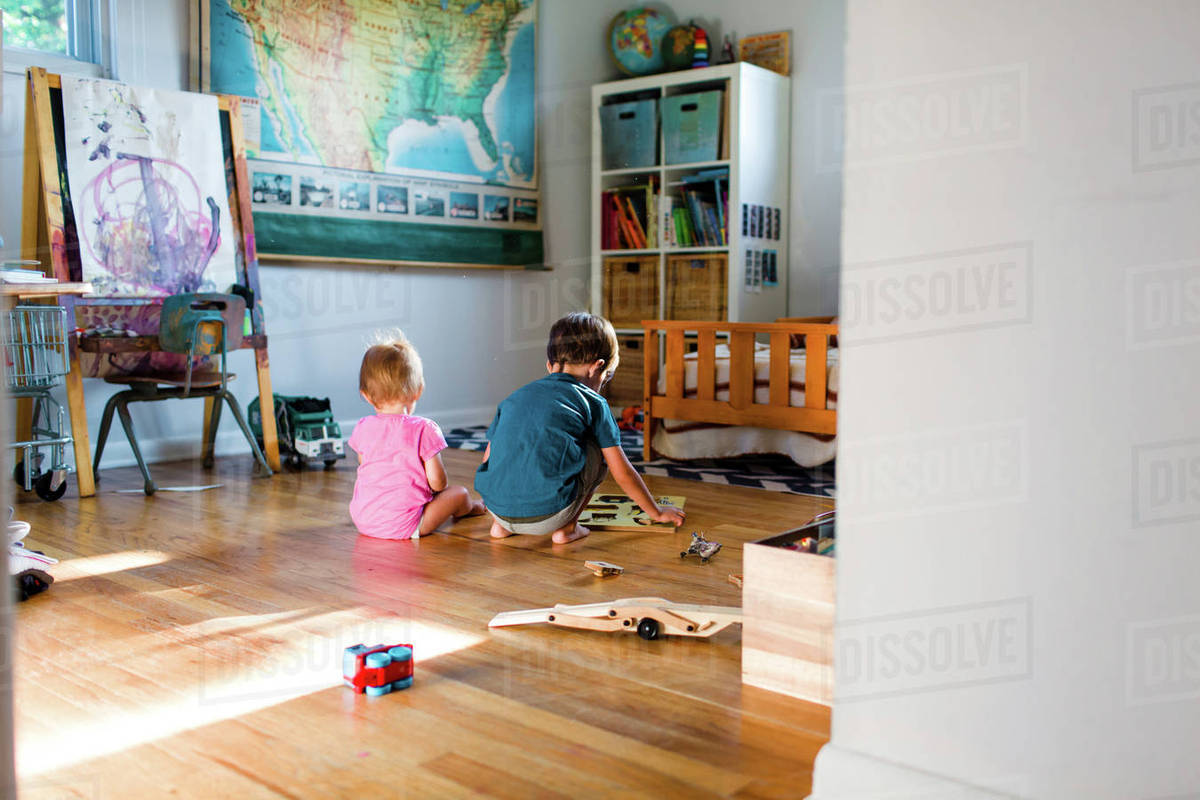 A brother and sister playing with a puzzle on the floor of a children\'s  bedroom. stock photo