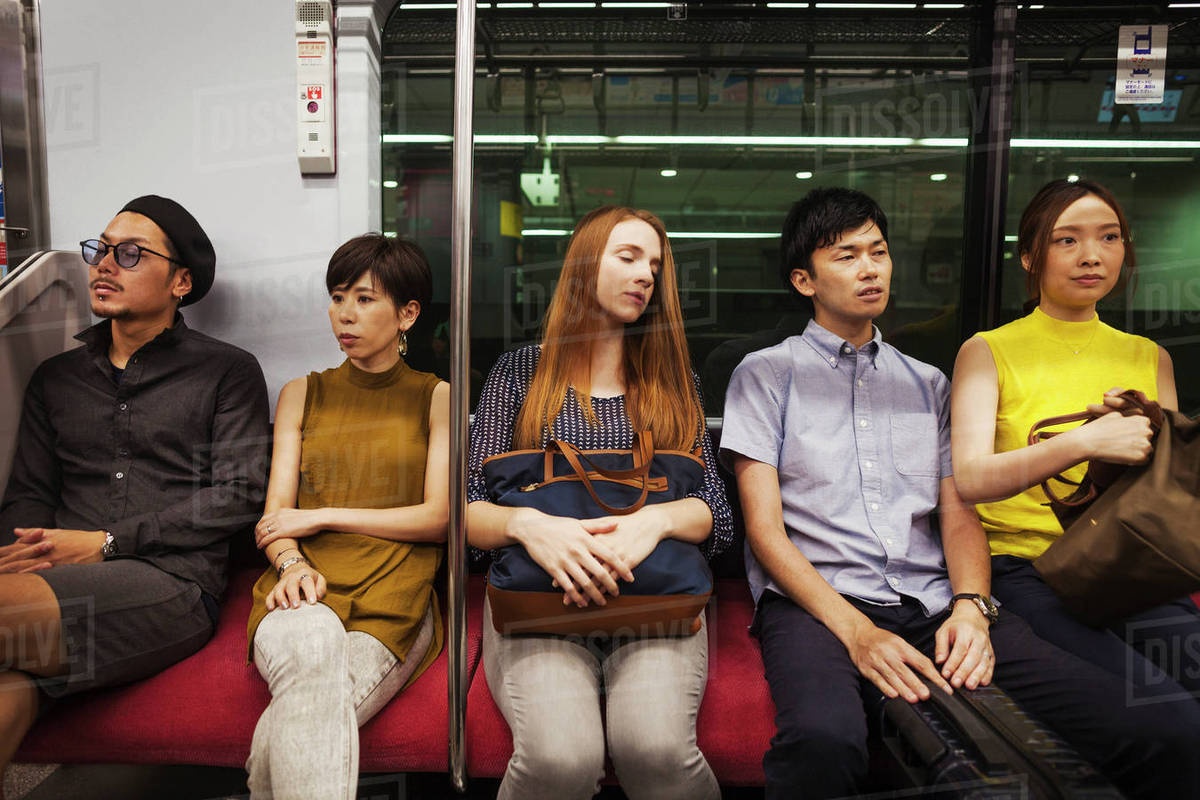 Five people sitting sidy by side on a subway train, Tokyo ...