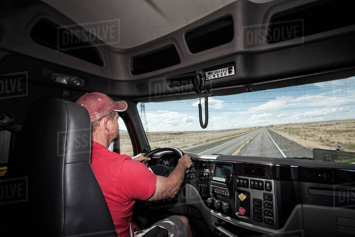 Interior cab view of a Caucasian man driving his commercial truck  stock  photo