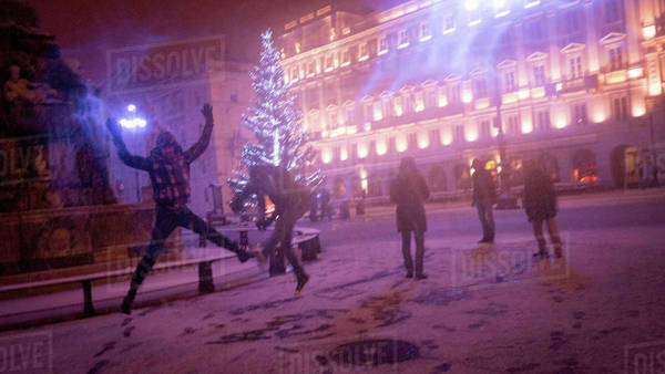Group of friends having fun in a snowstorm at night in Trieste, Italy Royalty-free stock photo