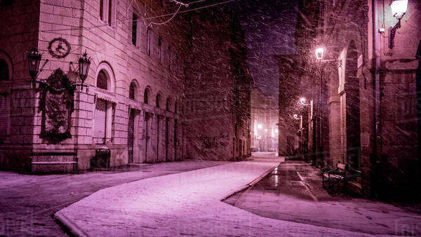 An empty street at night during a snowstorm in Trieste, Italy Royalty-free stock photo